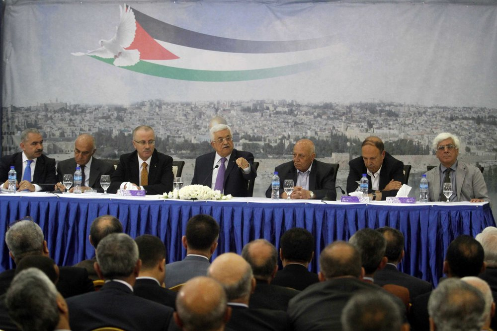 Palestinian Authority (PA) President Mahmoud Abbas (center) attends a meeting of Palestinian businessmen in Ramallah April 29, 2014. The Palestinian National Fund, often in partnership with the PA, pays salaries to imprisoned Palestinian terrorists and their families. Credit: Issam Rimawi/Flash90.