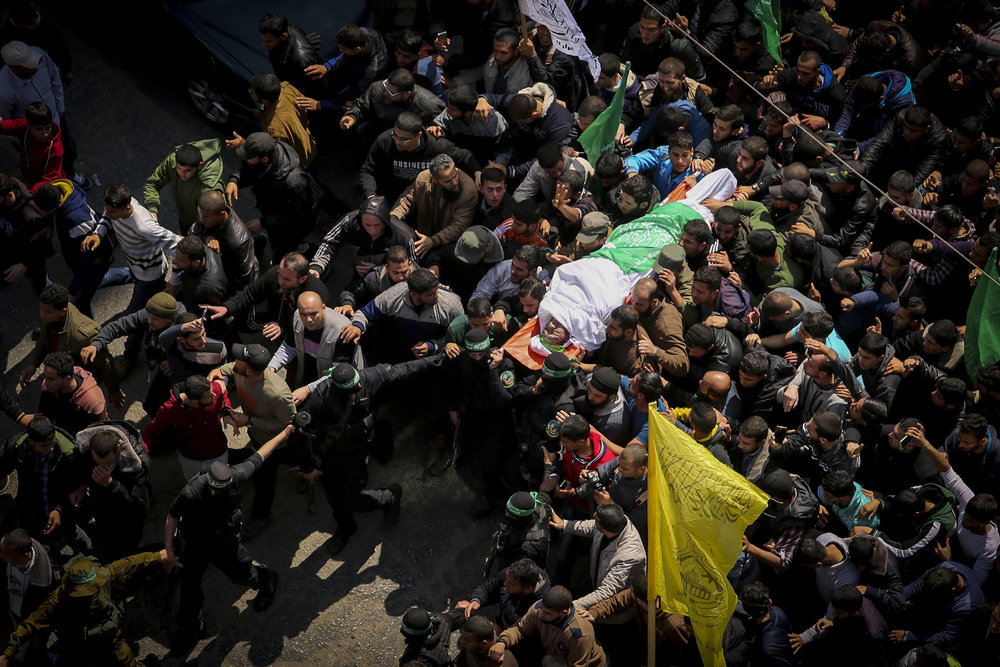 Masked terrorists from Hamas's Izz ad-Din al-Qassam Brigades carry the body of slain terror commander Mazen Faqha during his funeral in Gaza City Saturday, March 25. Credit: Abed Rahim Khatib/Flash90.