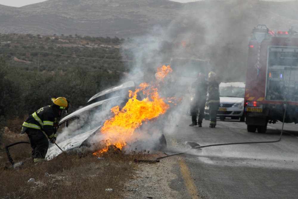 Firefighters put out a blaze from a burning car belonging to Israeli Jews near the West Bank village of Tuqua Nov. 8, 2013. In the attack, an Israeli woman sustained light-to-moderate wounds, and one of her children was lightly injured, after a firebomb was hurled at their vehicle near Tekoa in Gush Etzion. Credit: Gershon Elinson/Flash90.
