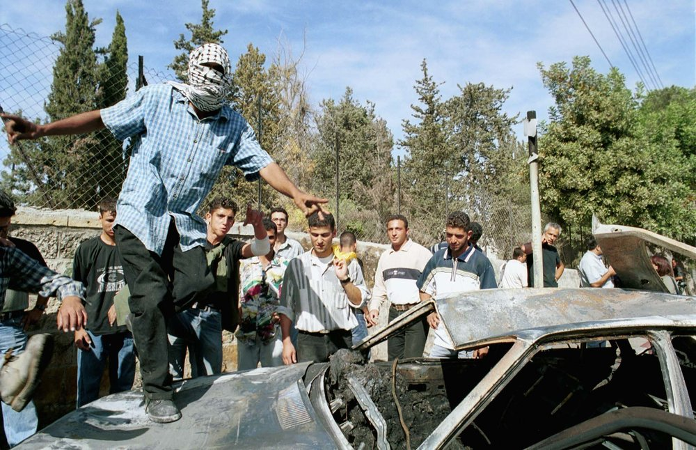 A Palestinian celebrates on top of the burned car of two Israeli soldiers who were lynched in Ramallah Oct. 12, 2000. Seventeen years later, one of the terrorists involved in the lynching was released early from prison this week. Credit: Flash 90.