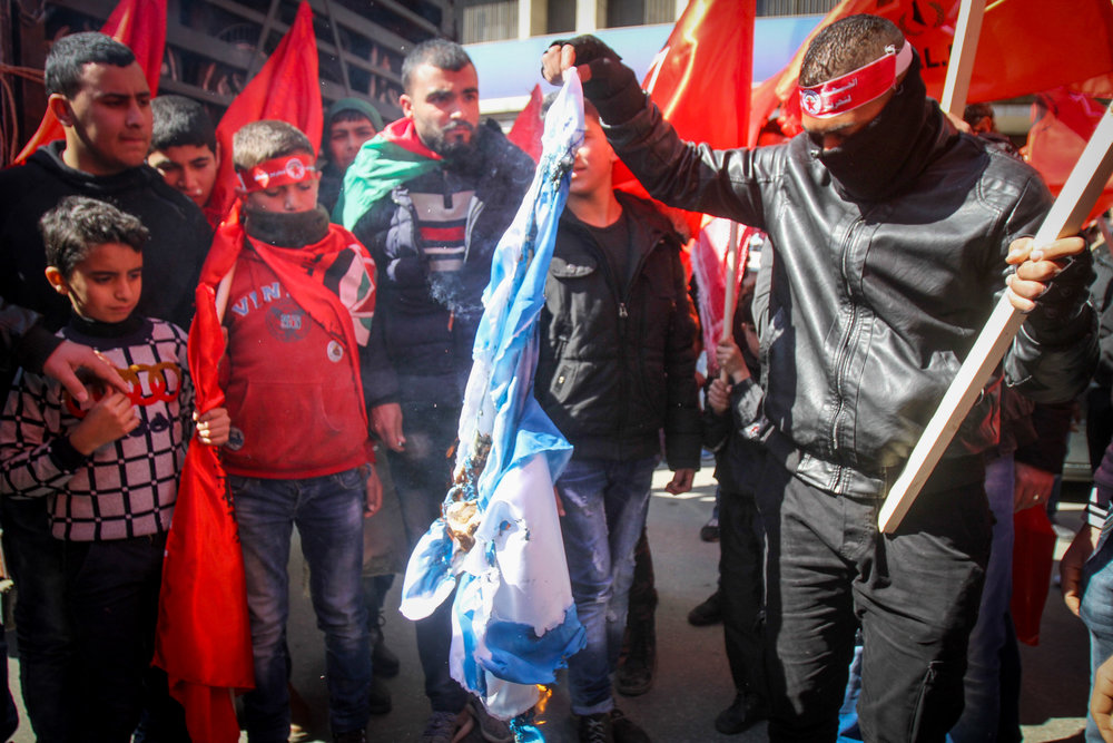 """Palestinian protesters burn an Israeli flag during a rally marking the 48th anniversary of the """"Democratic Front for the Liberation of Palestine"""" in the West Bank city of Nablus, Feb. 18, 2016. Credit: Nasser Ishtayeh/Flash90."""