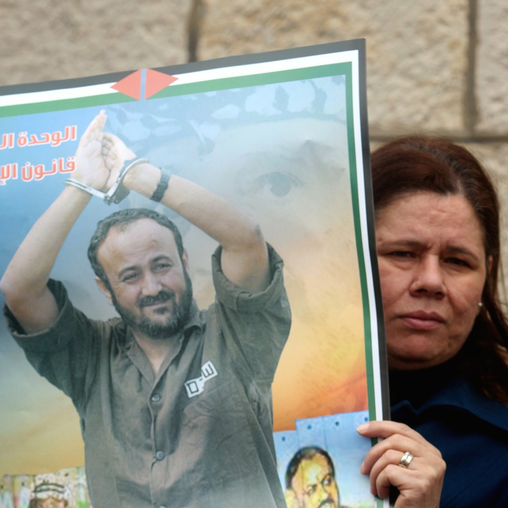 A Palestinian woman holds a portrait of Palestinian terrorist prisoner Marwan Barghouti during a rally in Ramallah, March 27, 2012. Credit: Issam Rimawi/Flash90.