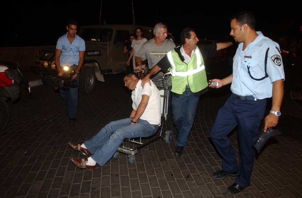 A wounded Israeli man is wheeled from Egypt to Israel, through the Taba border crossing, following a bombing at the Hilton Taba hotel in the Egyptian Sinai Peninsula, Oct. 7, 2004. Credit: Flash90.