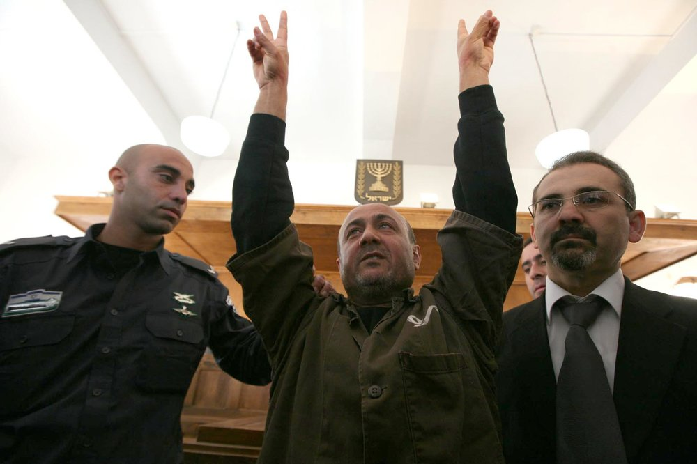 Palestinian terrorist Marwan Barghouti is escorted in handcuffs by Israeli police into Jerusalem's Magistrate Court Jan. 25, 2012. Credit: Flash90.