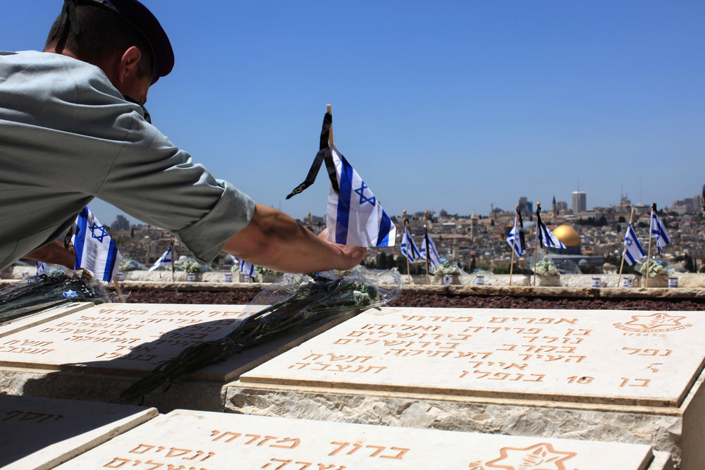 An Israeli soldier places a flag on the grave of a fallen soldier during preparations for Israel's Memorial Day services on the Mount of Olives, overlooking Jerusalem's Old City, in April 2009. Credit: Kobi Gideon/Flash90.