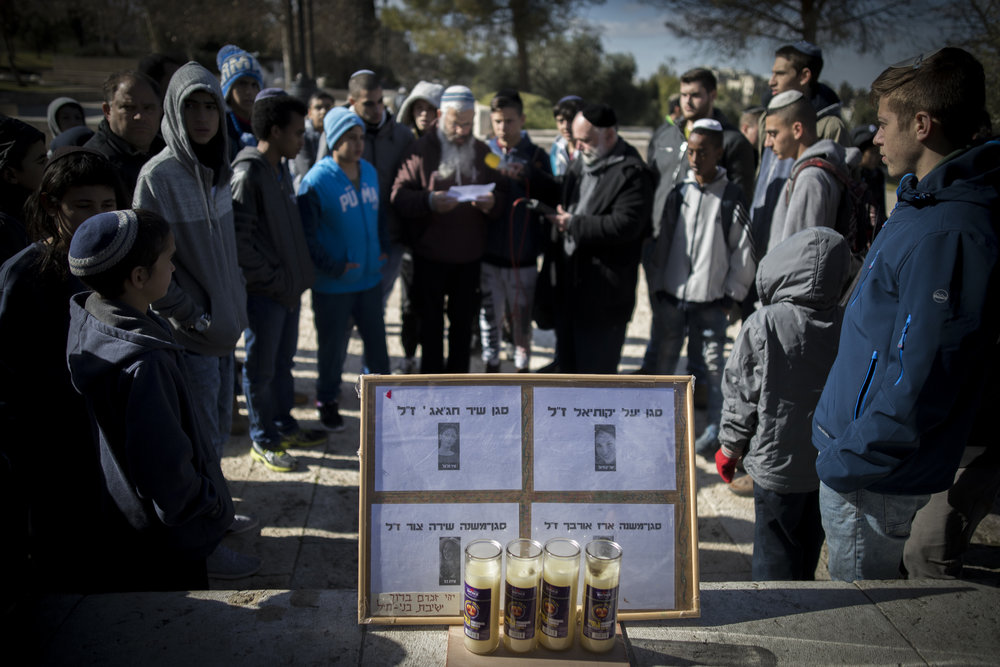 Memorial candles and pictures of the slain victims at the site of the January 2017 truck-ramming terror attack in Jerusalem's Armon Hanatziv neighborhood, as Israelis gather to mourn the four soldiers killed in the attack. Credit: Yonatan Sindel/Flash90.
