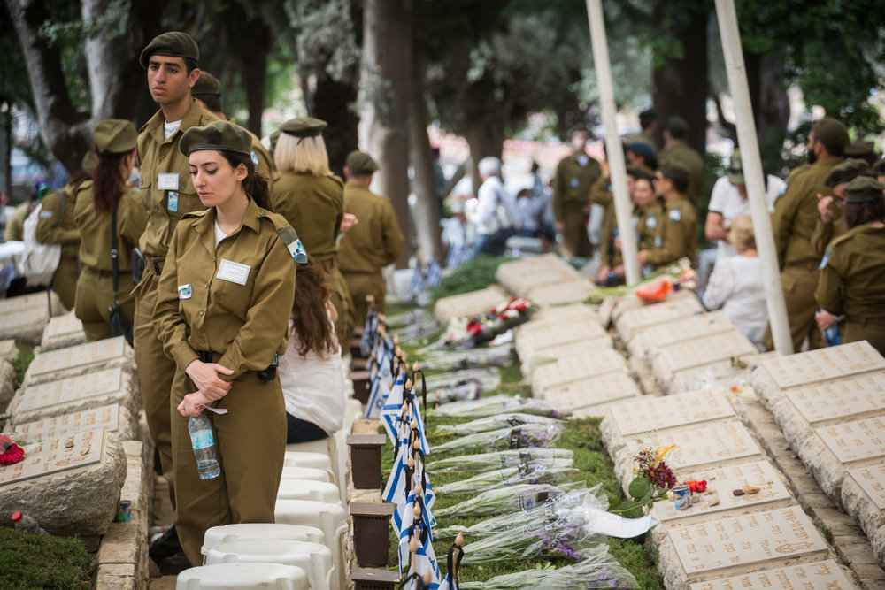 Current Israeli soldiers stand by the graves of fallen soldiers at the Kiryat Anavim military cemetery on Yom Hazikaron (Memorial Day) May 1, 2017. Credit: Hadas Parush/Flash90.