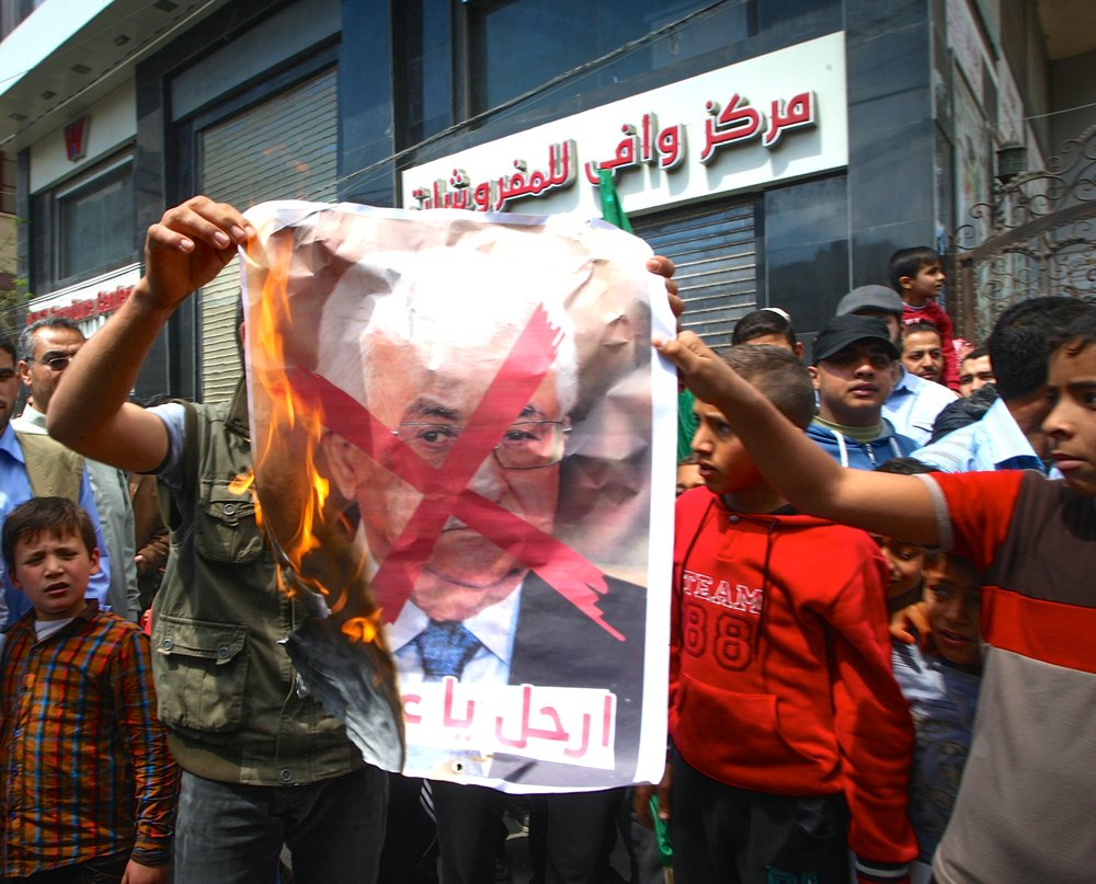 Palestinians burn a poster bearing a crossed-out image of Palestinian Authority (PA) President Mahmoud Abbas during a protest against both the Israeli government and the PA in the southern Gaza Strip, April 14, 2017. Credit: Abed Rahim Khatib/Flash90.