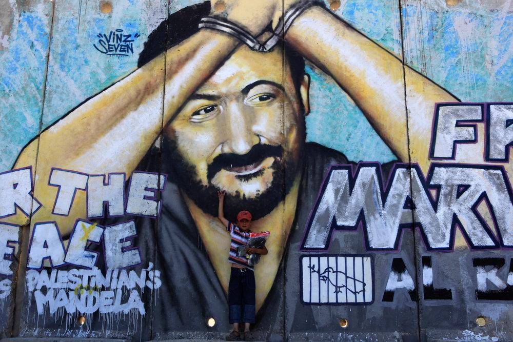 A Palestinian child stands in front of a mural depicting jailed Palestinian terrorist Marwan Barghouti. Credit: Kobi Gideon/Flash90.