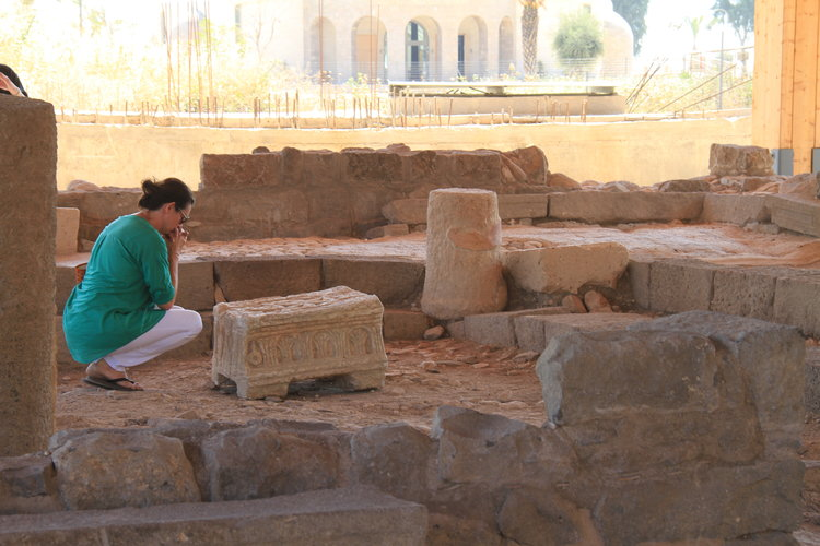 A woman prays next to the Magdala Stone. Credit: Magdala Center and Israel Antiquities Authority.