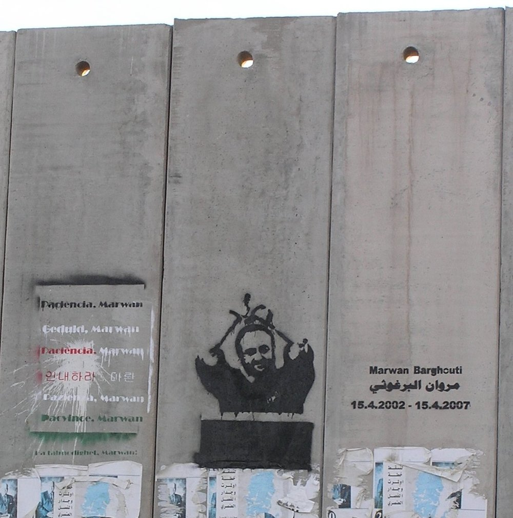 A portrait of Palestinian terrorist Marwan Barghouti on the security fence between Israel and the disputed territories. Credit: Eman via Wikimedia Commons.