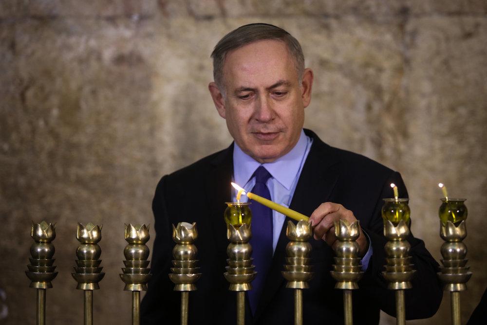 Israeli Prime Minister Benjamin Netanyahu lights a Hanukkah menorah at the Western Wall in Jerusalem, Dec. 25, 2016. Credit: Marc Israel Sellem/POOL/Flash90.