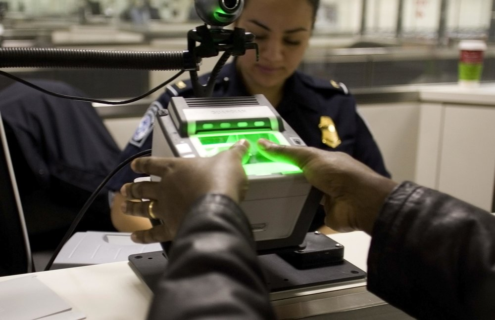 A traveler arriving at Washington Dulles International Airport uses the new US-VISIT mechanism that records fingerprint images. Credit: Gerald Nino/CPB via Wikimedia Commons.