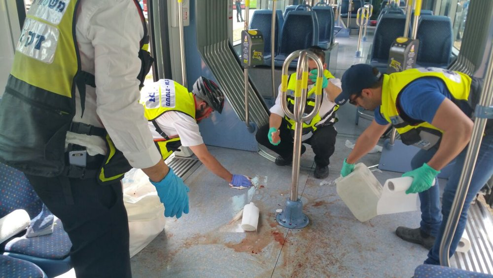 Israeli ZAKA emergency response volunteers clean up and collect remains at the scene of a Palestinian terror attack on the Jerusalem light rail in April 2017. Credit: Courtesy ZAKA.