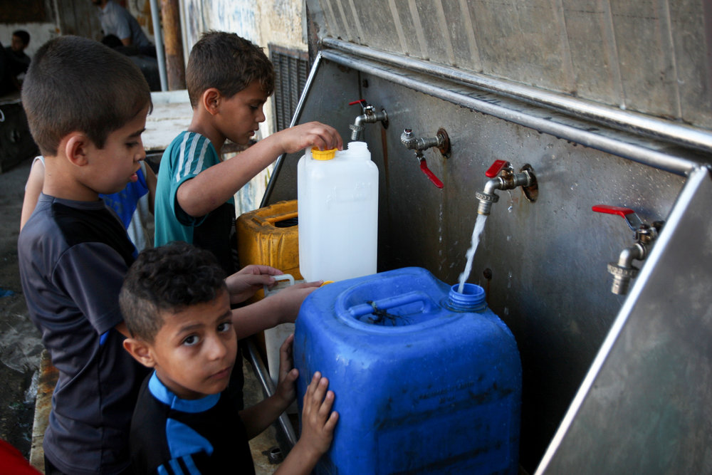 Palestinian children fill containers with drinking water from public taps in the southern Gaza Strip, June 11, 2017. Credit: Abed Rahim Khatib/Flash90.
