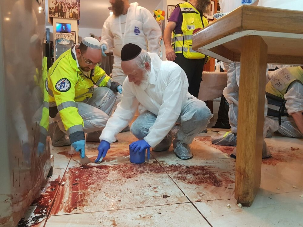 "The ZAKA volunteer emergency response group—including its chairman, Yehuda Meshi Zahav (pictured in front, center)—cleans up the scene of Friday night's deadly Palestinian terror attack at the Salomon family home in Halamish. Zahav said the ""scenes of a bloodbath…shocked us all to the core—even the most veteran ZAKA volunteers."" Credit: Yehezkiel Itkin/ZAKA."
