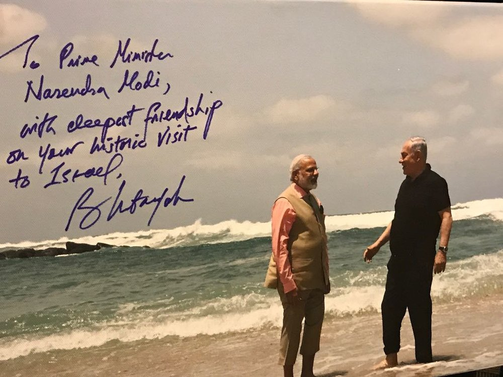 Indian Prime Minister Narendra Modi tweeted this photo of his beach walk with Israeli Prime Minister Netanyahu in July. The photo is hand-signed by Netanyahu. Credit: Twitter.