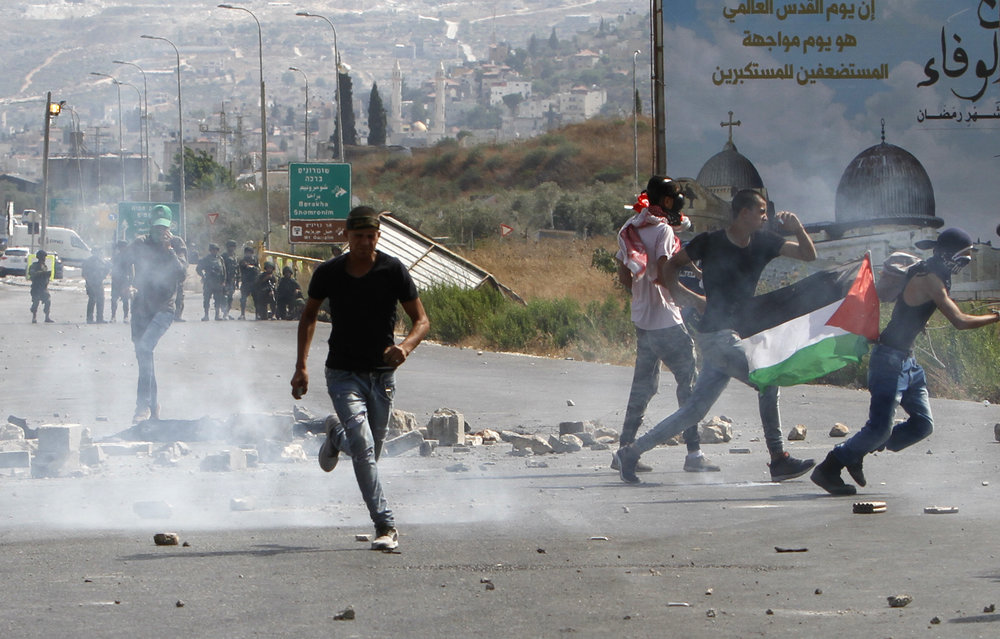 "Palestinians hurl stones at Israeli security forces during a demonstration at the Hawara checkpoint, near Nablus, amid Muslim riots over Jerusalem's Temple Mount holy site July 21, 2017. Israel Hayom last week quoted a Palestinian Authority security official as claiming that Iran's regime invested ""millions of shekels"" to inflame the tensions surrounding the Temple Mount. Credit: Nasser Ishtayeh/Flash90."