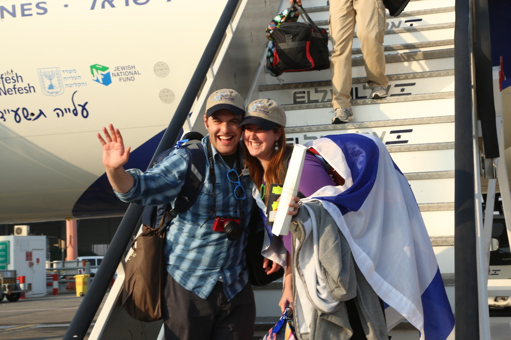 A happy couple makes aliyah as part of El Al Flight LY 3004, a Nefesh B'Nefesh chartered flight, in July 2014. Credit: Sasson Tiram.