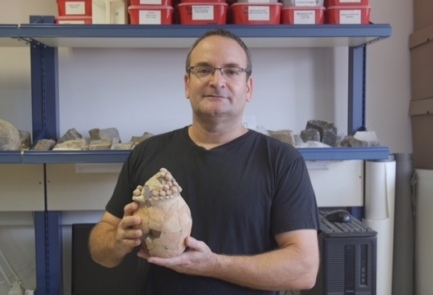 Prof. Danny Rosenberg of the Zinman Institute of Archaeology at the University of Haifa holds the seven-millennia-old vessel unearthed at Tel Tsaf. Credit: Courtesy of the University of Haifa.