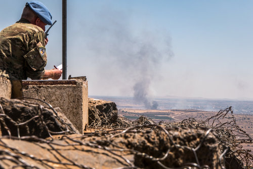 A United Nations observer is stationed at a lookout point as smoke rises in a Syrian village near the Israel-Syria border in the Golan Heights during Syrian Civil War fighting June 25, 2017. Credit: Basel Awidat/Flash90.