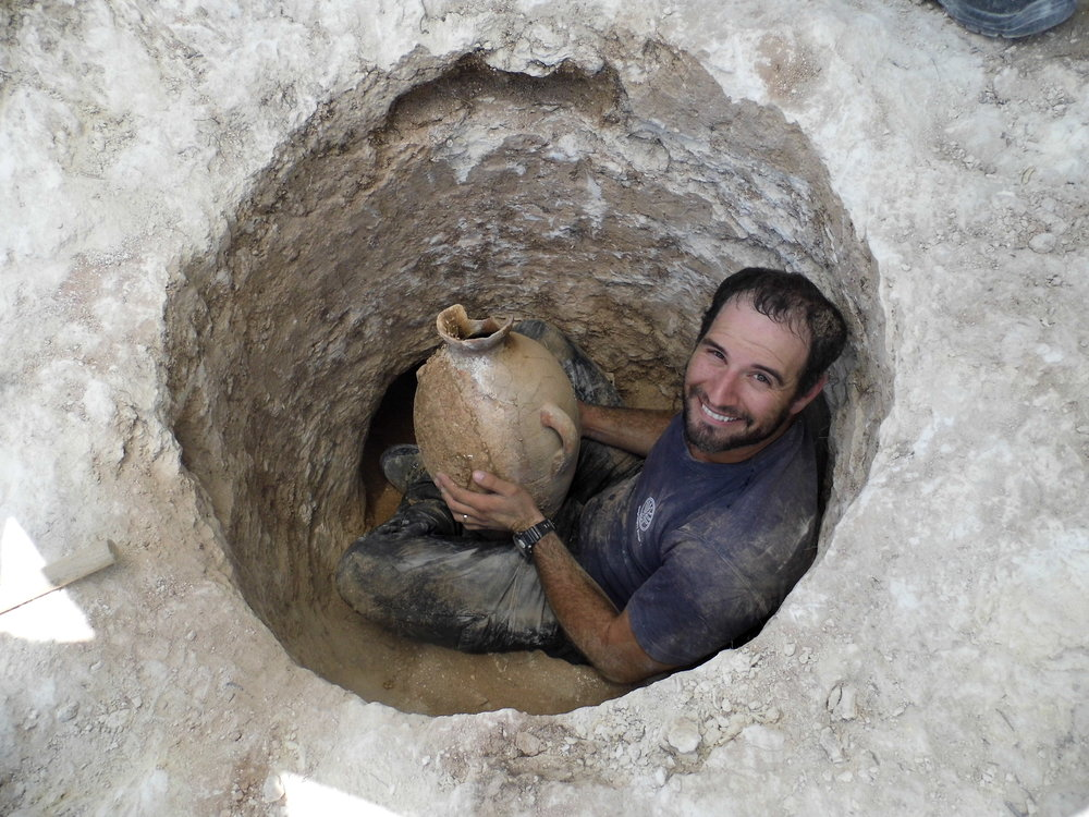 David Tanami, an Israel Antiquities Authority (IAA)archaeologist, works in a narrow tomb opening to bring out a 4,000-year-old jug. Credit: Shua Kisilevitz, IAA.