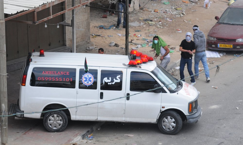 Palestinians throw rocks from behind an ambulance during a riot in Qalandiya. (Illustrative.) Credit: IDF.