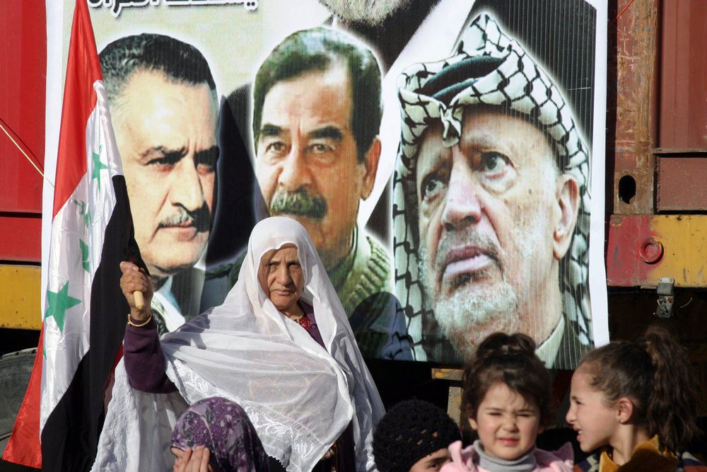 Palestinians commemorate the third anniversary of the death of Saddam Hussein during a rally in the town of Halhoul near Hebron on Jan. 15, 2010. Next to the picture of Hussein (center) is a photo of late Palestinian leader Yasser Arafat. Credit: Najeh Hashlamoun/Flash90.