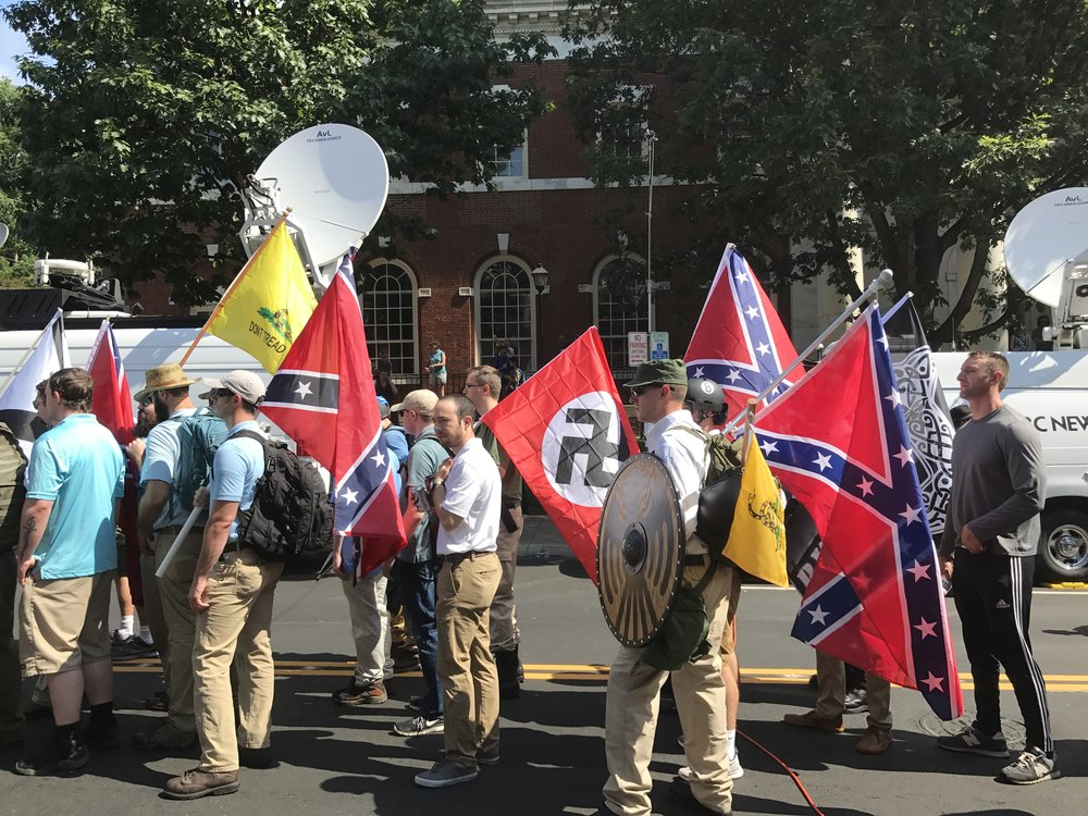 White supremacist protesters carry Nazi and Confederate flags in Charlottesville, Va., on Aug. 12. Credit: Anthony Crider via Wikimedia Commons.