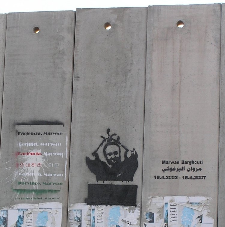 A portrait of Palestinian terrorist Marwan Barghouti on the security fence between Israel and the disputed territories. Israel has barred the entry of seven European officials who planned to meet Barghouti. Credit: Eman via Wikimedia Commons.