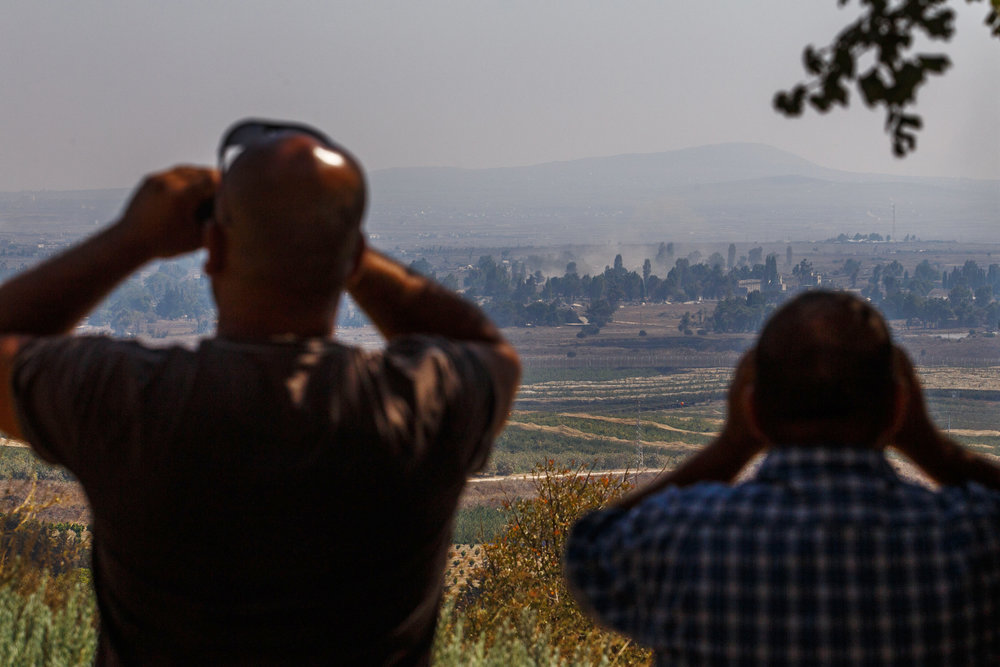 Israelis in the northern Golan Heights region watch smoke rise in Syria in September 2014. Credit: Flash90.