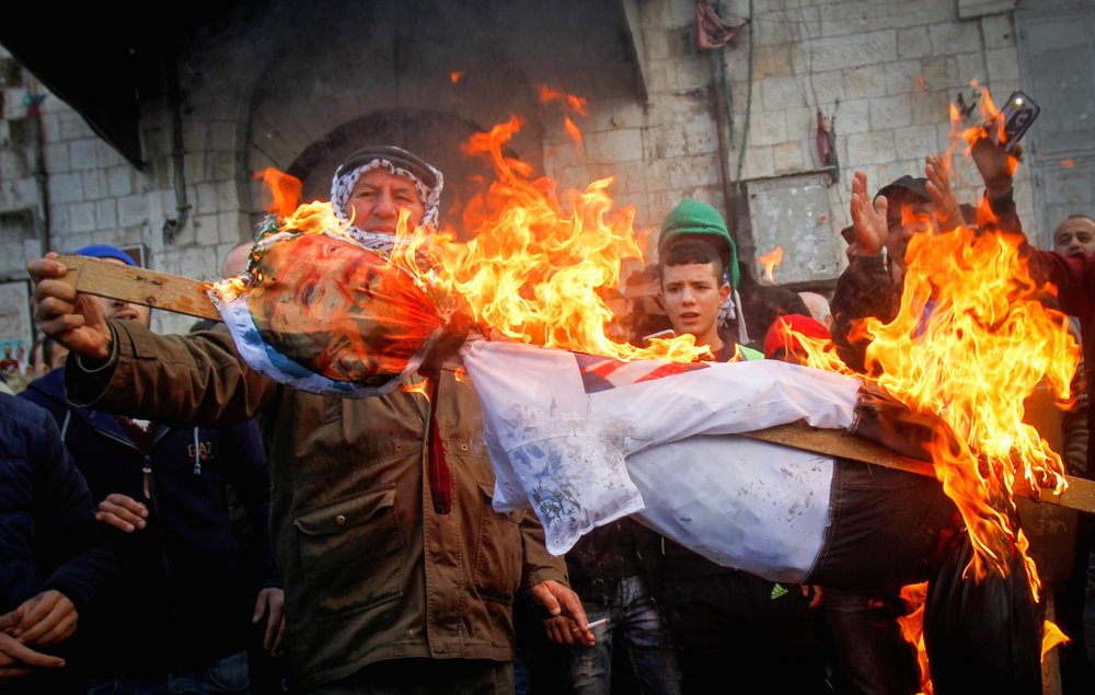 Palestinians in Nablus burn a poster of President Donald Trump on Dec. 7, in the aftermath of Trump's recognition of Jerusalem as Israel's capital. Credit: Nasser Ishtayeh/Flash90.