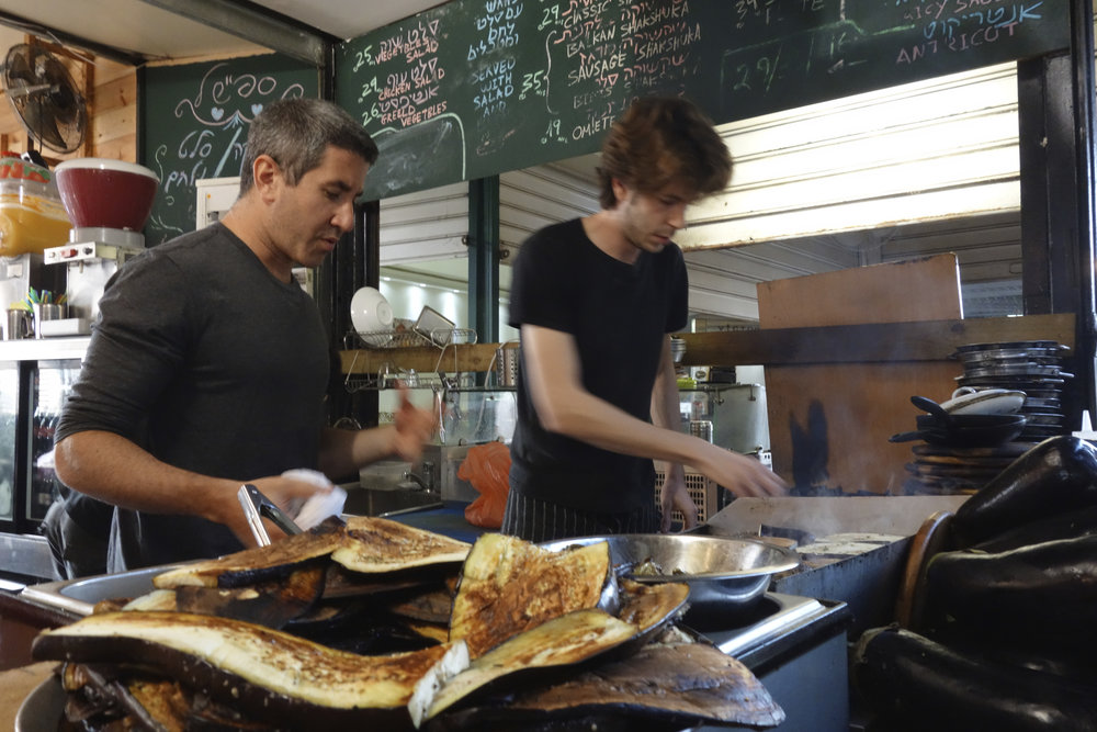 "Chef and restaurateur Michael Solomonov (left) at the Carmel Market in Tel Aviv. Credit: ""In Search of Israeli Cuisine"" press photo."