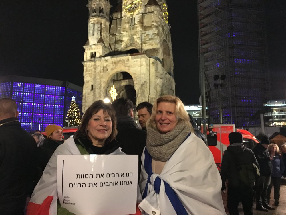 """During a Dec. 19 demonstration outside the Kaiser Wilhelm Memorial Church in Berlin, coinciding with the anniversary of the 2016 Christmas market terror attack in that city, the woman pictured at left holds a Hebrew-language sign reading, """"They love death, we love life."""" At right is Antje Böttinger, a non-Jewish German who wrapped herself in an Israeli flag. Credit: Orit Arfa."""
