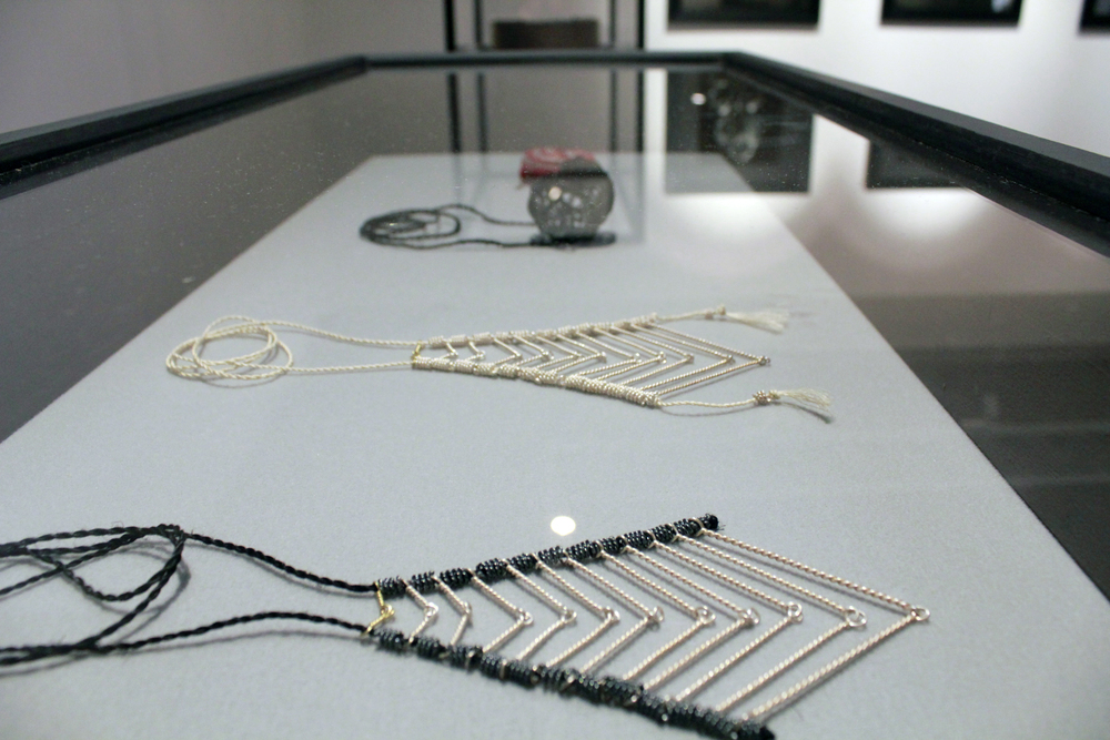 Installation of work during the exhibition showing   'Twelve' neckpieces (set of two),   Space pendant and   Weave brooch,
