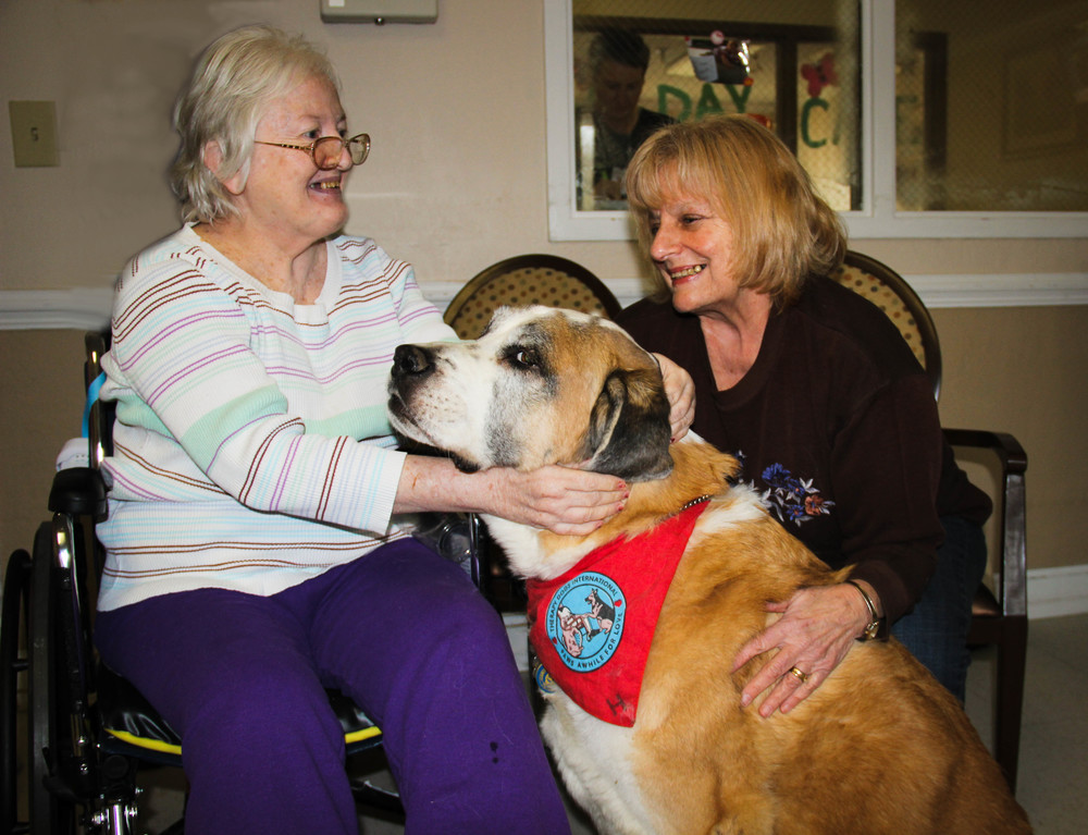 Good Shepherd parishioner Carole Webber and her certified therapy dog Henry visit Kathy Mixon, another parishioner.