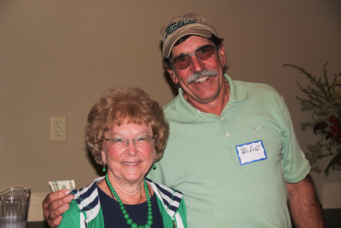 Honorary golf outing chairwoman Catherine Clark gives a door prize to golfer Pat List