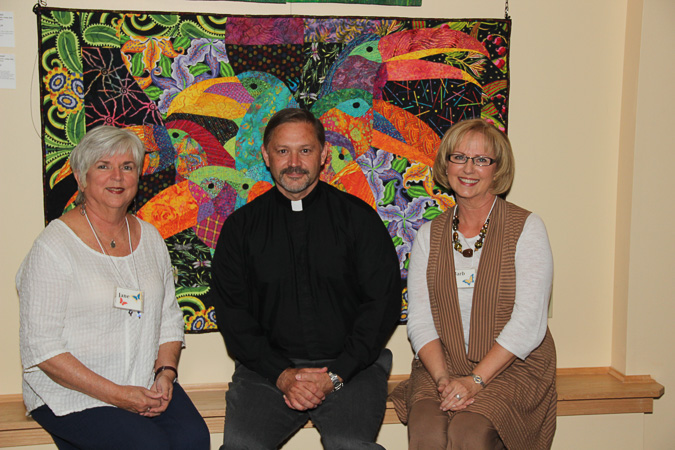 Jane Oliver and Barb Redmond, co-charis of the exhibition, with Fr. Bill Breedlove in front of Toucans by Lucinda Graber of Upland, CA.