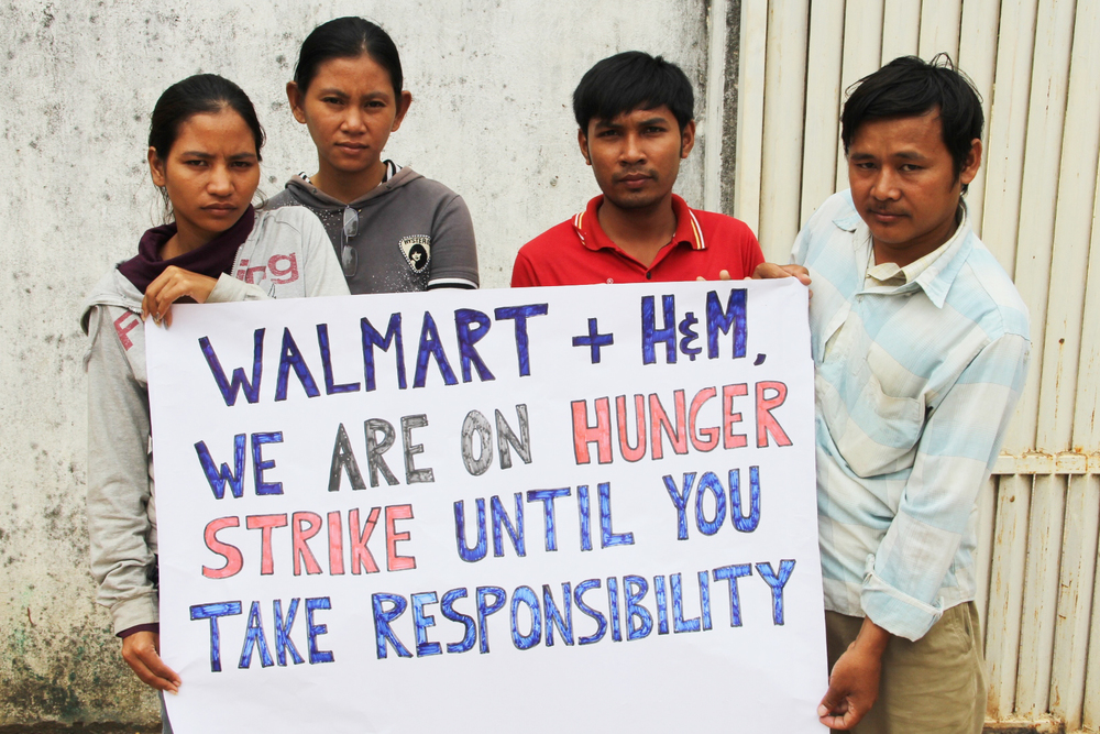 Hundreds of Phnom Penh workers camped outside their shuttered garment factory to demand Walmart and H&M pay them the wages they are owed.