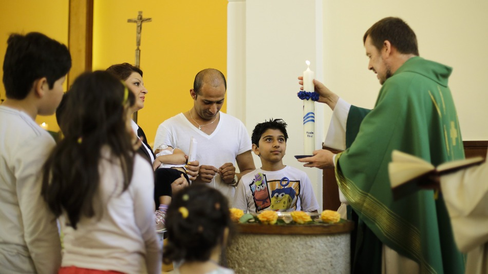 Pastor Gottfried Martens lights a candle during a service to baptize people from Iran, in the Trinity Church in Berlin. Third right is Iranian asylum-seeker Mohammed Ali Zanoobi. He is one of hundreds of mostly Iranian and Afghan asylum seekers who have converted to Christianity at the evangelical church. (Image: Markus Schreiber/AP)