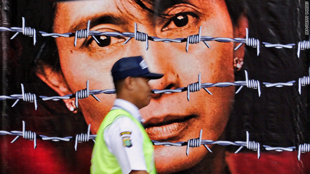 A guard walks past a huge poster of Aung San Suu Kyi (source: CNN)