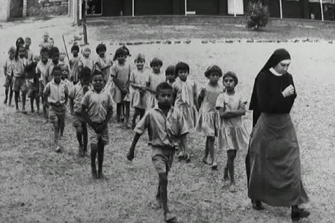 A nun leads aboriginal children away