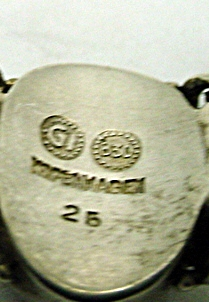 "This set of hallmarks combines the 830 silver mark with the GI and, unusally enough, the city ""COPENHAGEN"" The circled GI marking places it between 1915 and 1930. In this case the .830 silver mark would date it pre-1927, and the city mark was used between 1907-1915."
