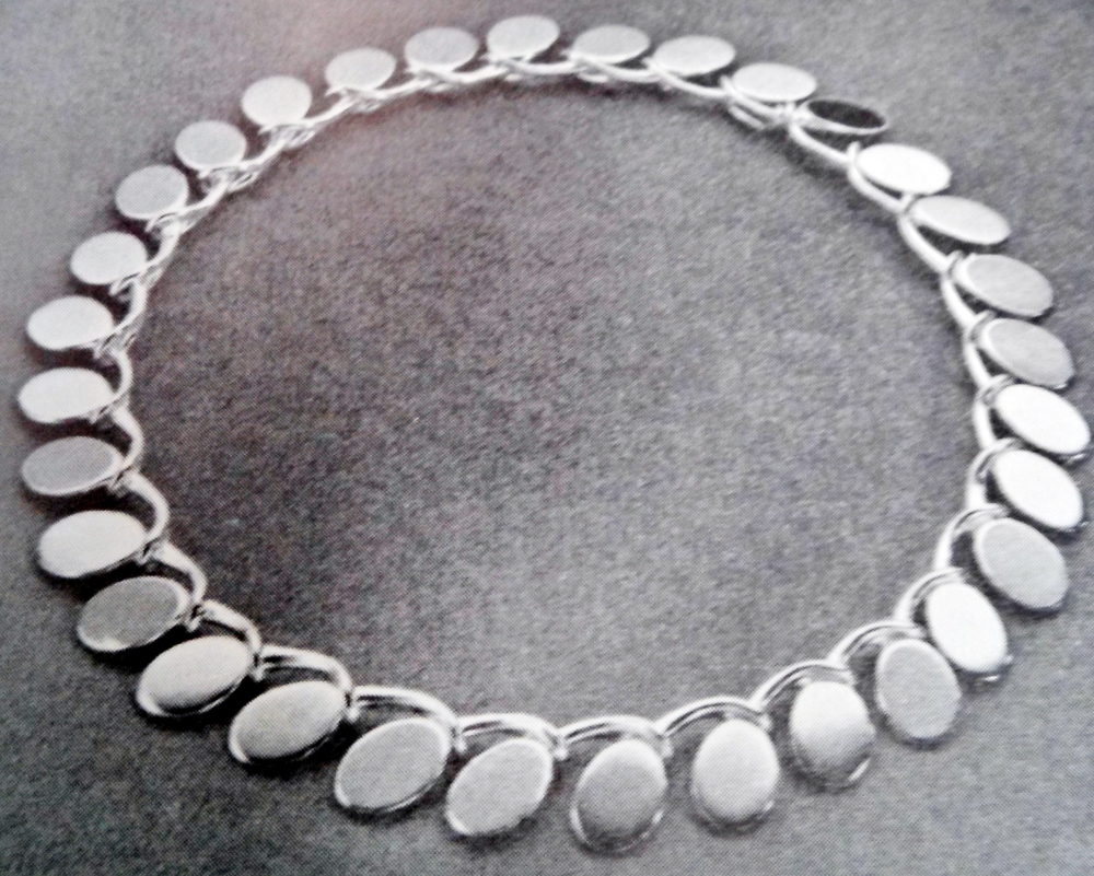 """The necklace shown in silver from Bent Gabrielsen was designed in 1957 for the Hans Hansen Silversmithy in Koldinghus. The necklace uses a clear yellow enamelling on the front, with black enamel on the clasp. Each link is identical to the next, and grasp each other like holding hands in a long chain. The piece represents a clearly thought out plan using an organic shapes to create interlocking  grommets and insert as part of the links, separating it from your average chain jewelry."" - Translated from the text accompanying the photo."