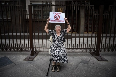 President of the Kremlin's human rights group,Lyudmila Alekseyeva, holding a sign that reads