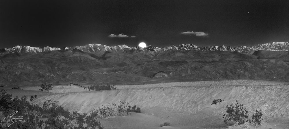 "In January 2010 I had gone to Death Valley. I was inspired by Ansel Adam's famous "" Moonrise in Hernandez new mexico 1941""   ( http://en.wikipedia.org/wiki/Moonrise,_Hernandez,_New_Mexico ) so I was looking for something like that in Black and white.      We went to the Dunes at 5 in the morning to shoot sunrise, on our way I saw this, so here it is my Version ""Moonrise in Death Valley 2010"""