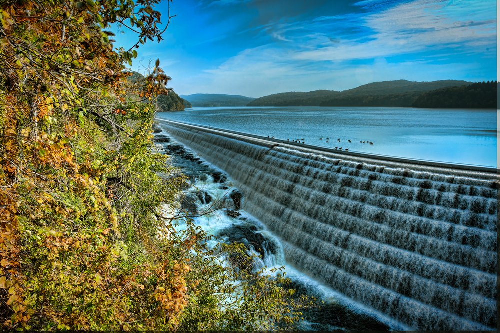 The New Croton Dam, part of the New York City water supply system, stretches across the Croton River near Croton-on-Hudson, New York, about 22 miles (35 km) north of New York City. Construction began in 1892 and was completed in 1906 Designed by Alphonse Fteley (1837–1903), this masonry dam is 266 feet (81 m) broad at its base and 297 feet (91 m) high from base to crest. Its foundation extends 130 feet (40 m) below the bed of the river, and the dam contains 850,000 cubic yards (650,000 m3) of masonry. The engineers' tablet mounted on the headhouse nearest the spillway lists the spillway length as 1,000 feet (300 m) and the total length of the dam and spillway combined as 2,188 feet (667 m). At the time of its completion, it was the tallest dam in the world. New Croton Dam impounds up to 19 billion US gallons (72,000,000 m3) of water, a small fraction of the New York City water system's total storage capacity of 580 billion US gallons (2.2×109 m3). The dam, in Westchester County, has an unusual spillway, part artificial and part natural, which forms a waterfall on the north side of the structure. New Croton Dam has a public park and trail head at its base and a road along its crest. Road use is limited to pedestrians and emergency vehicles.