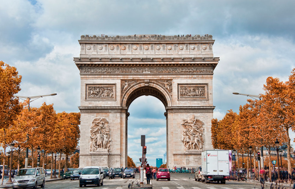 """TheArc de Triomphe(Arc de Triomphe de l'Étoile) is one of the most famous monuments inParis. It stands in the centre of thePlace Charles de Gaulle(originally namedPlace de l'Étoile), at thewestern end of theChamps-Élysées.[3]There is a smaller arch, theArc de Triomphe du Carrousel, which stands west of theLouvre. TheArc de Triomphe(in English: """"Triumphal Arch"""") honours thosewho fought and died for France in theFrench Revolutionaryand theNapoleonic Wars, with the names of all French victories and generals inscribed on its inner and outer surfaces. Beneath its vault liestheTomb of the Unknown Soldierfrom World War I. TheArc de Triompheis the linchpin of the historic axis (Axe historique) – a sequence of monuments and grand thoroughfares on a route which goes from the courtyard of the Louvre, to theGrande Archede la Défense. The monument was designed byJean Chalgrinin 1806, and itsiconographicprogram pittedheroically nudeFrench youths against beardedGermanicwarriors inchain mail. It set the tonefor public monuments, with triumphant patriotic messages. The monument stands 50 metres (164 ft) in height, 45 m (148 ft) wide and 22 m (72 ft) deep. The large vault is 29.19 m (95.8 ft) high and 14.62 m (48.0 ft) wide. The small vault is 18.68 m (61.3 ft) highand 8.44 m (27.7 ft) wide. It is the second largesttriumphal archin existence (afterArch of Triumph in Pyongyang).[4]Its design was inspired by the RomanArch of Titus. TheArc de Triompheis socolossal that three weeks after the Paris victory parade in 1919, (marking the end of hostilities in World War I),Charles Godefroyflew hisNieuportbiplane through it, with the event captured on newsreel"""