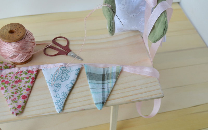 Finally, the friends arranged the flags in a line, and sewed it together with a binding of folded ribbon. They left enough ribbon on each end to tie the bunting to a branch.