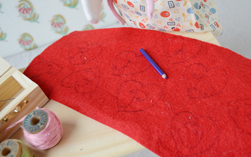 Lucy took some red felt, and drew heart-shaped designs on it. The designs were not too complicated, just some hearts and the first letters of her friends' names. But she was careful to make the letters as pretty as she could.